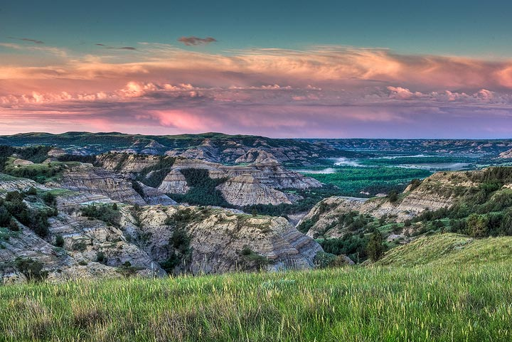 Sunrise light over the grass covered badlands of the Little Missouri River Valley in the North Unit of Theodore Roosevelt National...